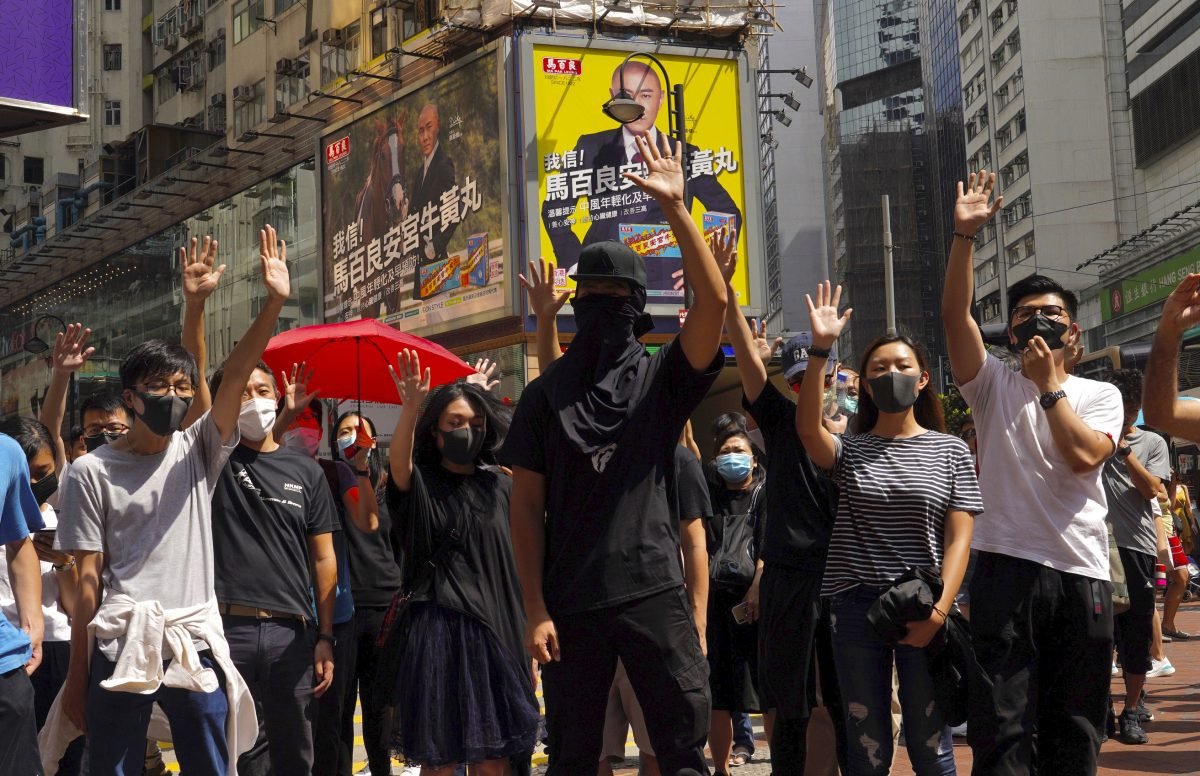 Protesters wear masks and hold up their hands