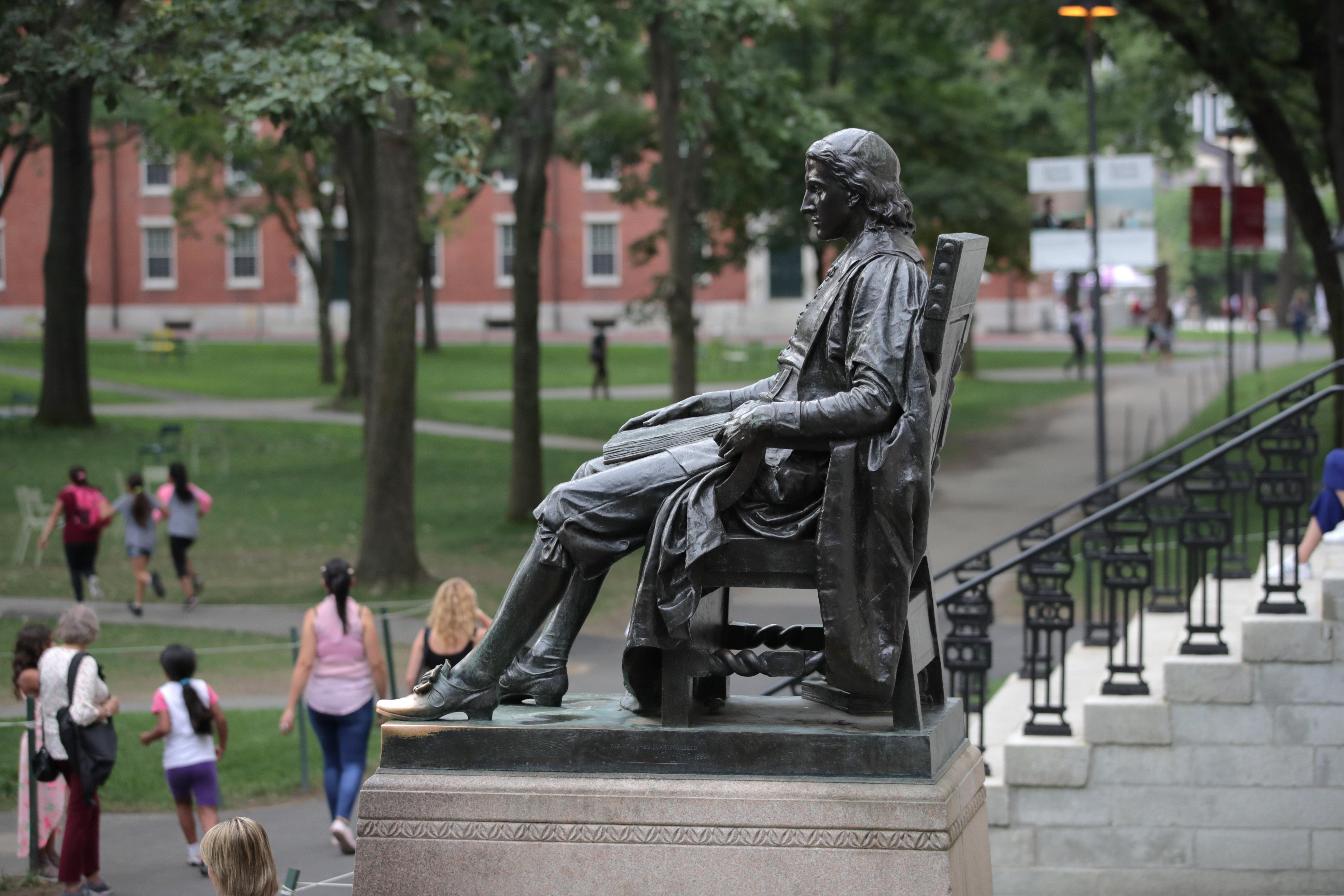 The statue of John Harvard sits in Harvard Yard at Harvard University in Cambridge, Mass., on Aug. 13, 2019. (AP Photo/Charles Krupa)