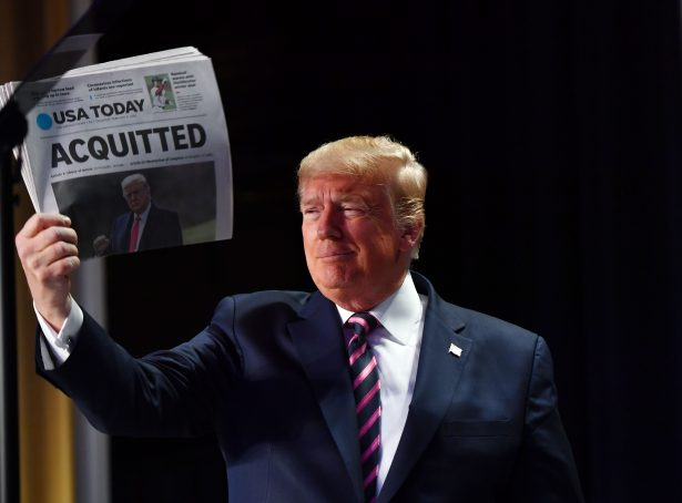 President Donald Trump holds up a newspaper